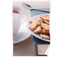 Cookies on old book next to a white cup of tea Poster