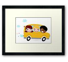 School children riding in a school bus Framed Print