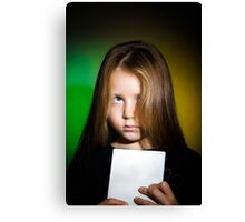 Cute little girl with long hair showing book, on colorful background Canvas Print