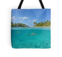 Half above and below island with sharks underwater Tote Bag
