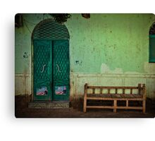 Bench against a wall Canvas Print