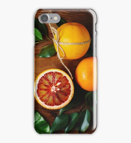 Orange fruit among green leaves on wooden table iPhone Case/Skin