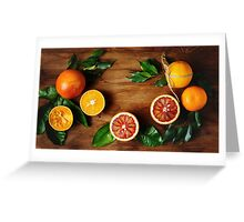 Orange fruit among green leaves on wooden table Greeting Card