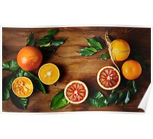 Orange fruit among green leaves on wooden table Poster