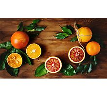 Orange fruit among green leaves on wooden table Photographic Print