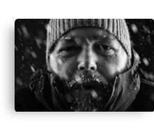 Freezing cold man standing in a snow storm blizzard Canvas Print