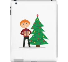 Boy with a gift in hands near the Christmas tree iPad Case/Skin