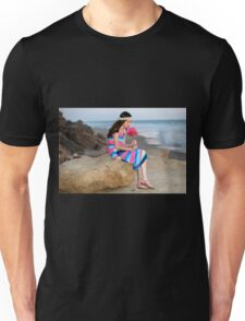 Preteen in colourful dress holds a flower bouquet while siting and waiting on the beach  Unisex T-Shirt