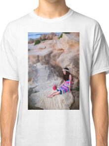 Preteen in colourful dress holds a flower bouquet while siting and waiting on the beach  Classic T-Shirt