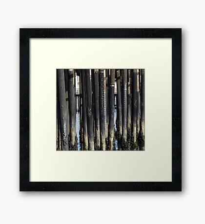 Weathered posts in the Ocean Framed Print