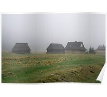 Old wooden cottages in the mountains. Spooky landscape in the mist Poster