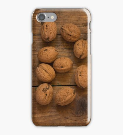 Letter B made from walnuts on a wooden table.  iPhone Case/Skin