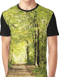 A pathway covered by leaves in a dense forest with filtered rays of light IV Graphic T-Shirt