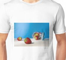 Close up of a strawberry and a glass jar full of strawberries lying down on a table Unisex T-Shirt
