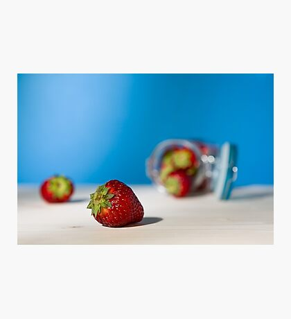 Close up of a strawberry and a glass jar full of strawberries lying down on a table Photographic Print