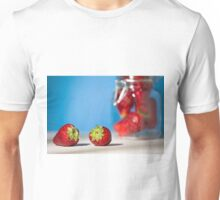 Close up of two strawberries on a table with blue background Unisex T-Shirt
