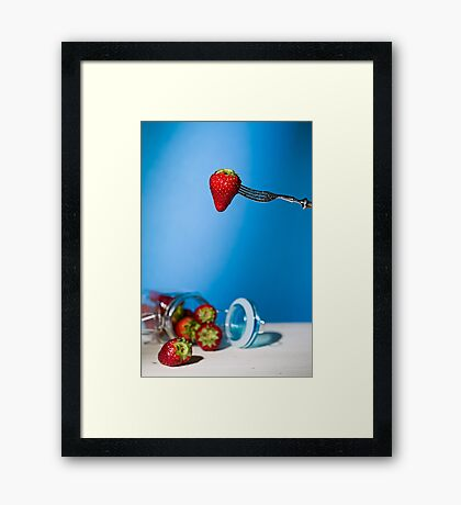 Strawberry suspended from a fork and under a jar of strawberries Framed Print