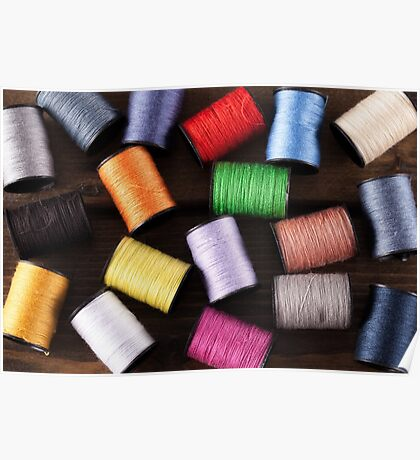 Colorful cotton reels scattered on wood Poster