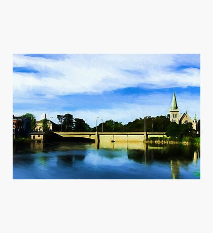Small town with church on river bank Photographic Print