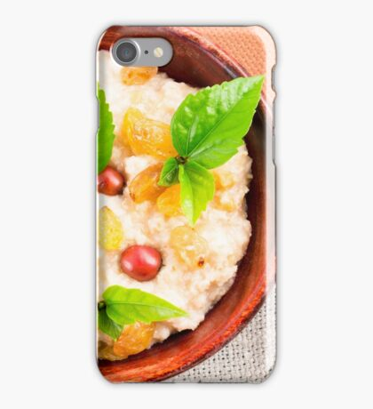 Old wooden bowl of healthy oatmeal with berries iPhone Case/Skin