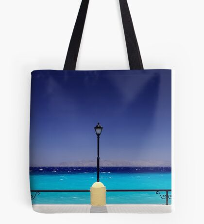 Turquoise sea with dark blue sky and a pylon in Greece Tote Bag