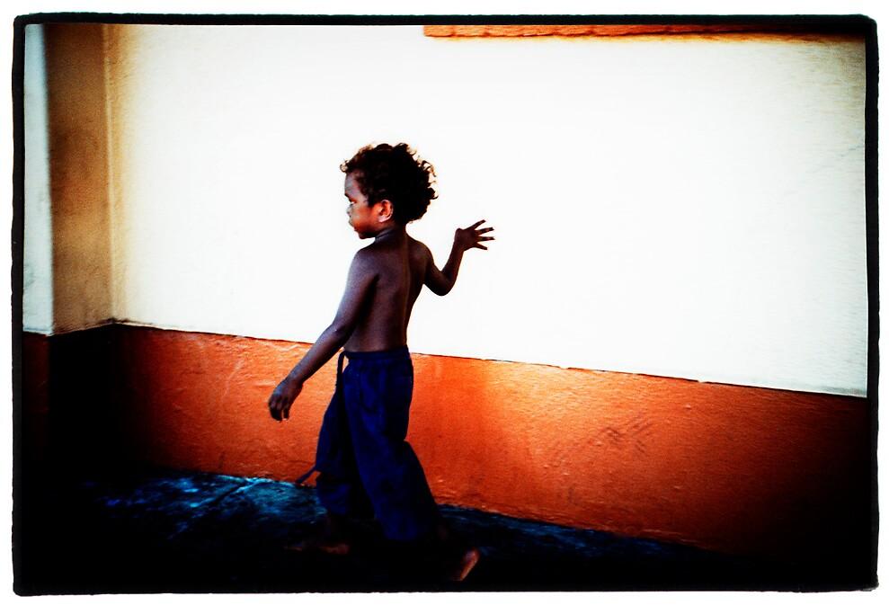 Boy against orange wall by Brett Squires