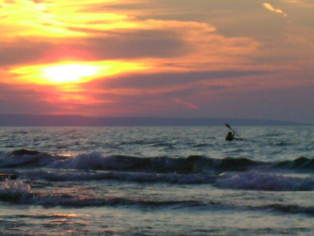 Kayaker at sunset by Robert Lake