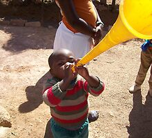 African child plays with toy horn by mnewmark84