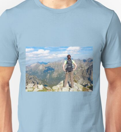 Woman with backpack standing on the edge, looking at mountains Unisex T-Shirt