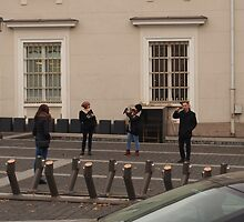 Three amateur photographers snapping girl photomodel. by miniailov