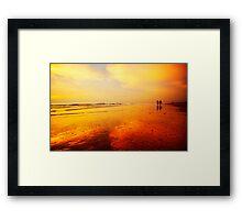 People walking on the beach Framed Print