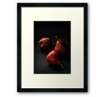 Red pears over dark background Framed Print