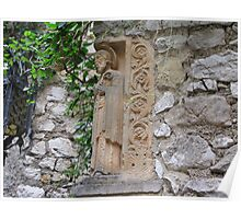 Saint Francis statue embedded into an stone wall in a enchanting medieval village in France Poster