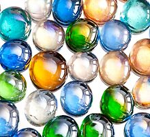 multicolored glass balls or marbles mix on white by Arletta Cwalina