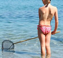 Little girl with fishing net on a sunny beach by alloverglad