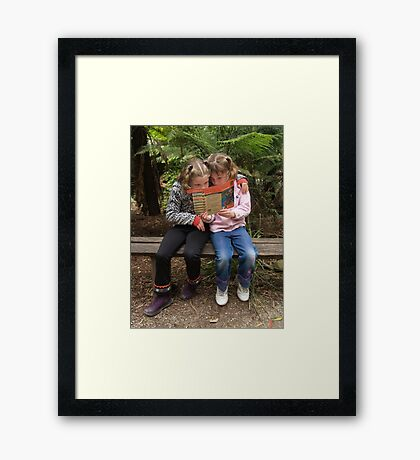 Girls looking at map Framed Print