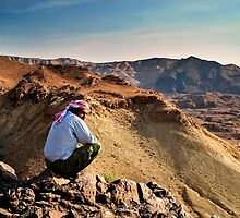 A local beduin looks out over the desert mountains by PhotoStock-Isra