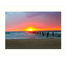 Poles in the sea the remains of a wharf at sunset Art Print