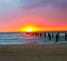 Poles in the sea the remains of a wharf at sunset by PhotoStock-Isra