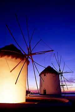 Greece. Mykonos Town. Illuminated windmills at dusk. by Steve Outram