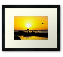 Silhouette of a man fishing on a beach at sunset Framed Print