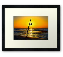 A fishing rod on the shore at sunset  Framed Print