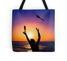 Silhouette of a man juggling on a beach at sunset  Tote Bag