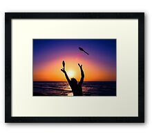 Silhouette of a man juggling on a beach at sunset  Framed Print