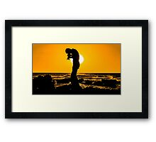 Silhouette of a photographer taking pictures on a beach at sunset Framed Print