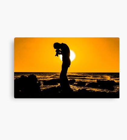Silhouette of a photographer taking pictures on a beach at sunset Canvas Print