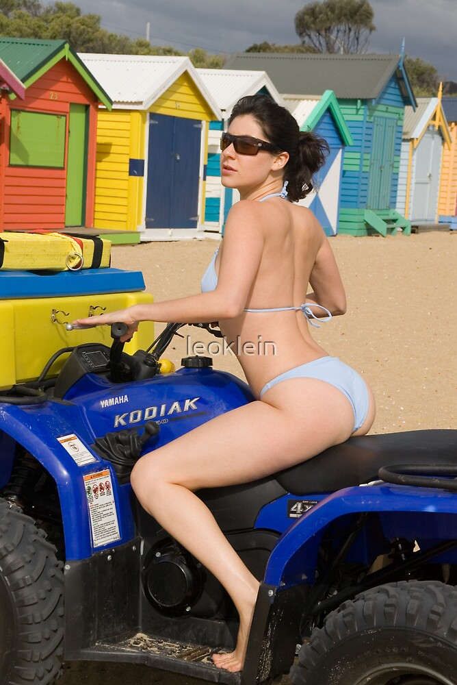 Female bikini model on rescue ATV at Brighton Beach in front of the bathing boxes by leoklein