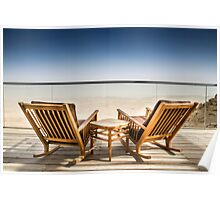 Deckchairs on a wooden deck overlooking a vast barren landscape.  Poster