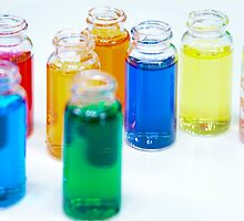 Glass bottles with coloured liquid at a Cosmetics manufacturer by PhotoStock-Isra