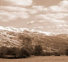 rocky mountain and fields countryside snow scene by morrbyte